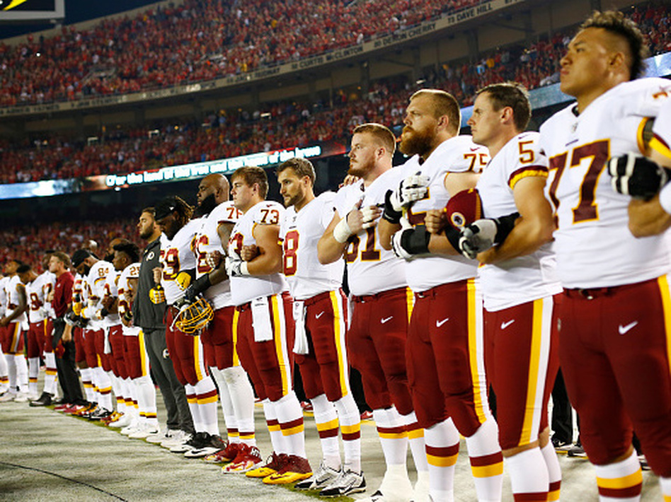 The Washington, D.C., football team stands at attention while linked in arms during the national anthem before Monday night's game against the Kansas City Chiefs at Arrowhead Stadium in Kansas City, Mo. (Jamie Squire/Getty Images)