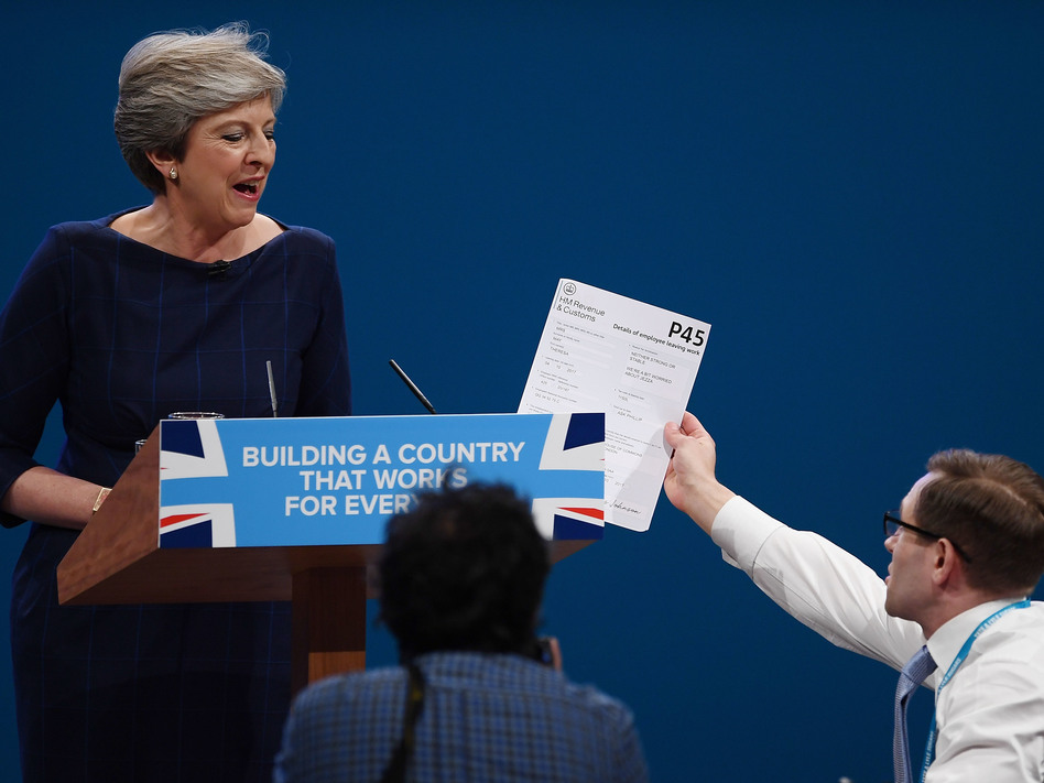 Comedian Simon Brodkin, also known as Lee Nelson, hands Prime Minister Theresa May a P45 form — the equivalent of a pink slip — during her speech at the Conservative Party Conference in Manchester. (Carl Court/Getty Images)