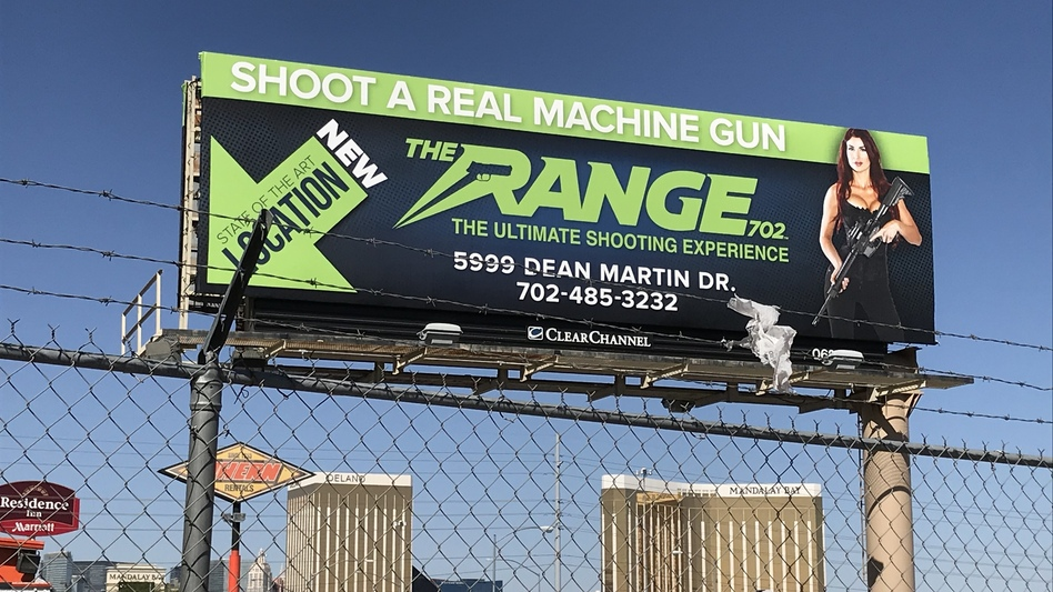 A billboard advertising a gun tourism business in Las Vegas hovers above the Mandalay Bay Hotel, site of a mass shooting Sunday night that killed 58 people and injured nearly 500. (Monika Evstatieva/NPR)