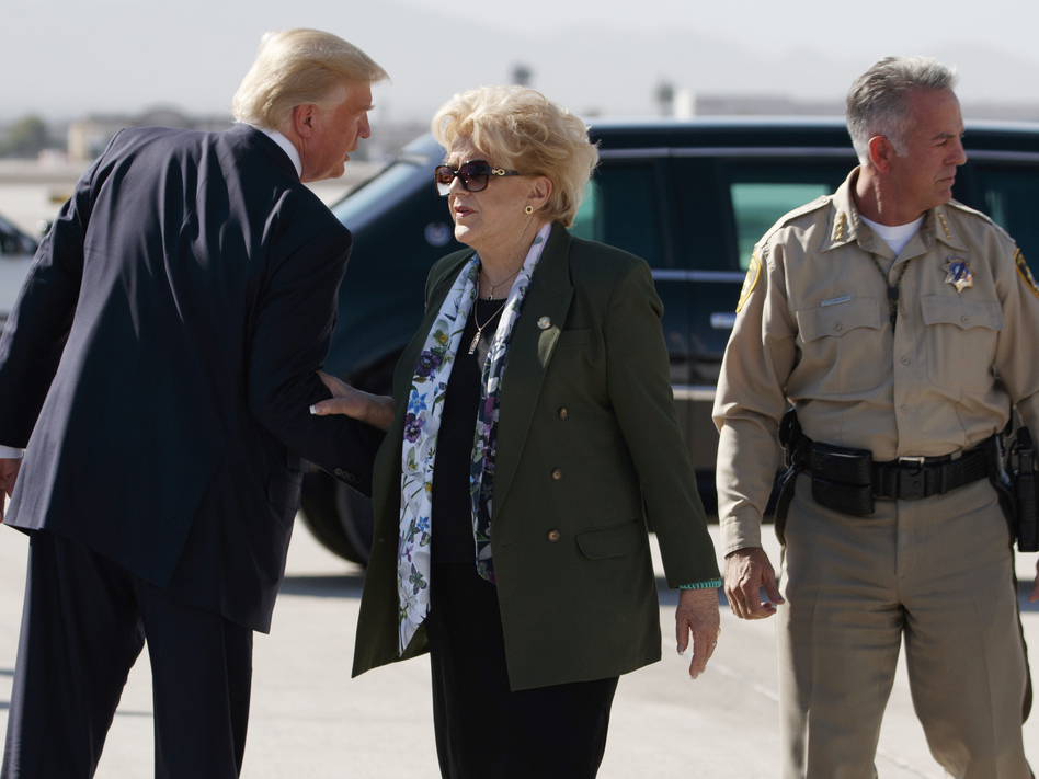 President Trump talks with Las Vegas Mayor Carolyn Goodman and Clark County Sheriff Joseph Lombardo (right) after arriving at Las Vegas McCarran International Airport on Wednesday to meet with victims and first responders of the mass shooting. (Evan Vucci/AP)