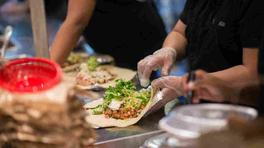 Employees prepare lunch orders at a Chipotle Mexican Grill restaurant at Madison Square Park in New York, U.S., on Wednesday, Jan. 29, 2014. Chipotle Mexican Grill Inc. is expected to release earnings figures on Jan. 30. Photographer: Craig Warga/Bloomberg via Getty Images
