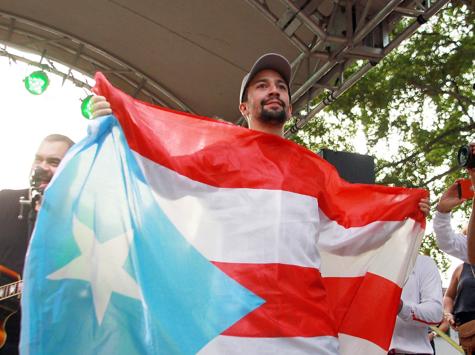 Lin-Manuel Miranda holds up the flag of Puerto Rico during a celebration in Vega Alta in August. (Gladys Vega/Getty Images)