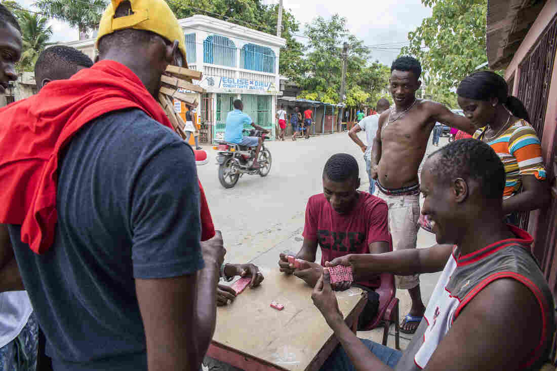 Men play dominoes by the street in Dosmond, Haiti.