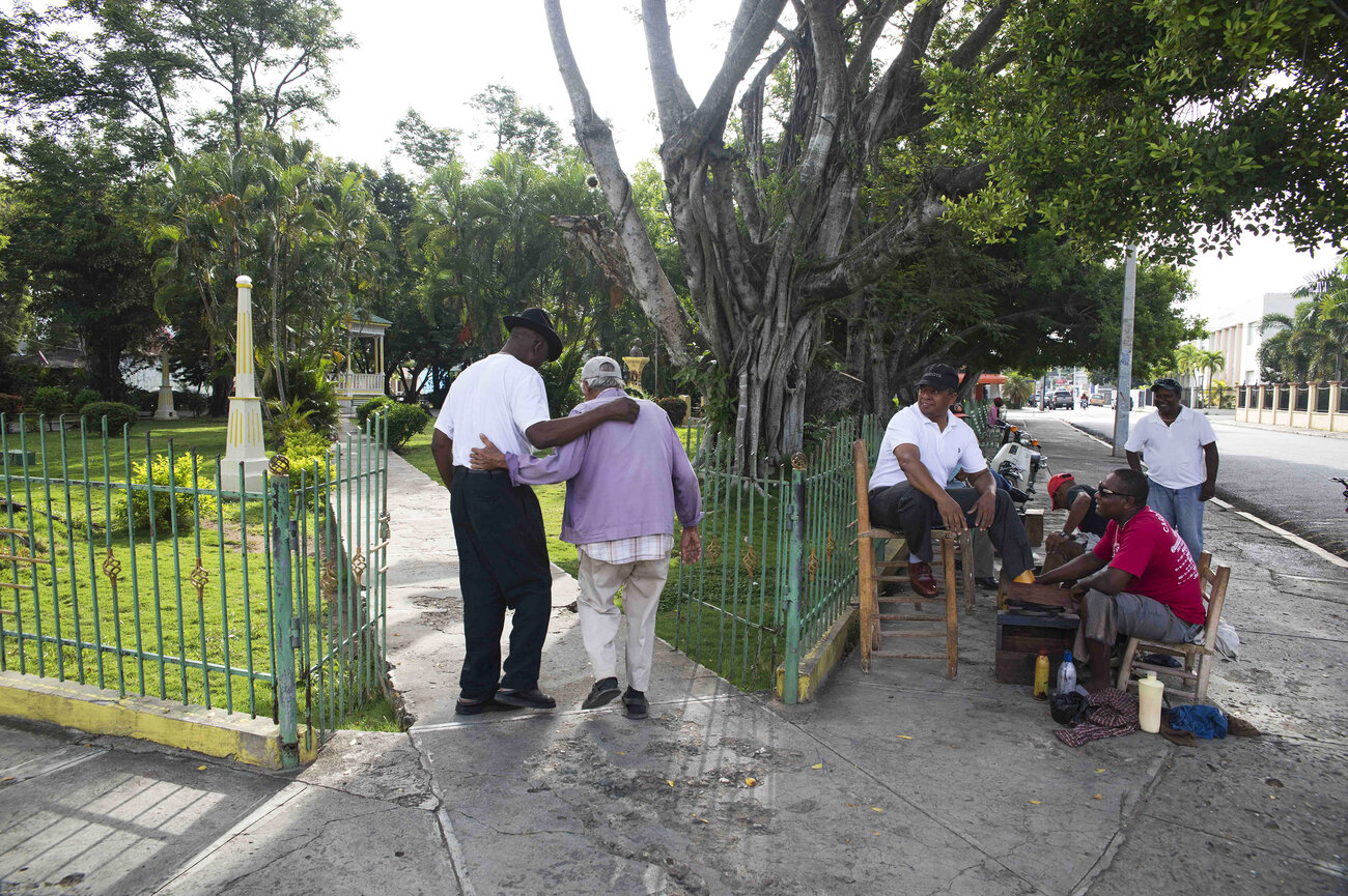 Men get their shoes shined at the Juan Pablo Duarte Park in Dajabon, Dominican Republic.