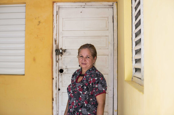 Nancy Betances stands outside the house she grew up in with her mother and grandfather, in Loma de Cabrera, Dominican Republic. Nancy's grandfather was a Dominican man who carried out some of the murders during the 1937 Massacre.