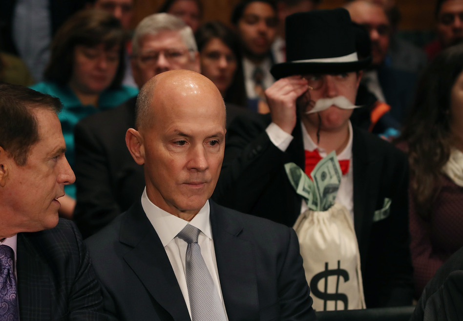 As former Equifax CEO Richard Smith prepares to testify before the Senate Banking Committee on Capitol Hill on Wednesday, activist Amanda Werner looks on through a monocle. (Mark Wilson/Getty Images)