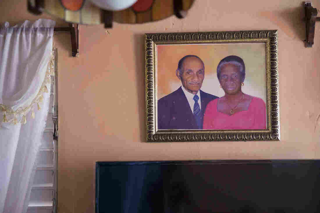 A portrait of Paulina Recio, 84, and her late husband hangs in her home in Restauracion, Dominican Republic.