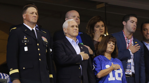 Vice President Pence and his wife, Karen, stand for the national anthem before Sunday