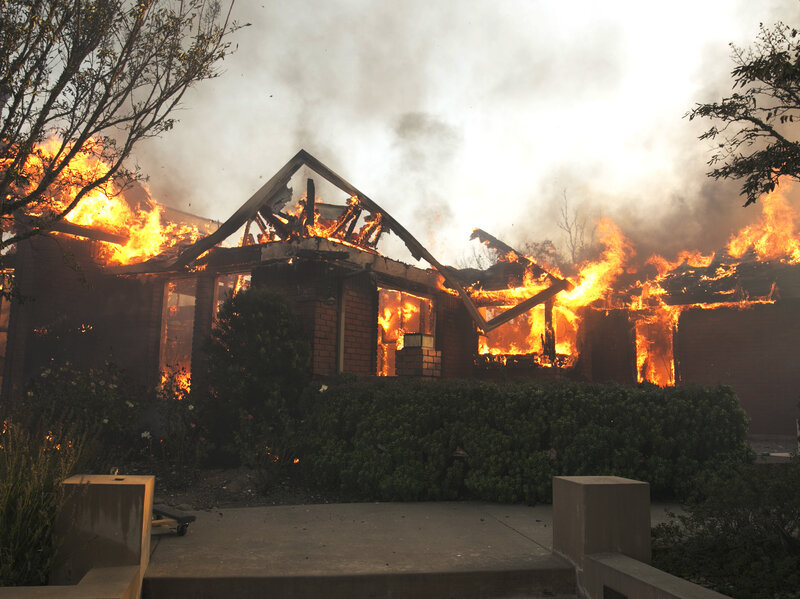 Flames from a wildfire consume a home Monday, east of Napa, Calif.     (Rich Pedroncelli/AP)