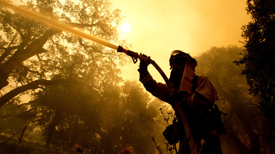 Napa County firefighter Jason Sheumann sprays water on a home as he battles flames from a wildfire on Monday in Napa, Calif. Wildfires whipped by powerful winds swept through Northern California sending residents on a headlong flight to safety through smoke and flames as homes burned. (Rich Pedroncelli/AP)