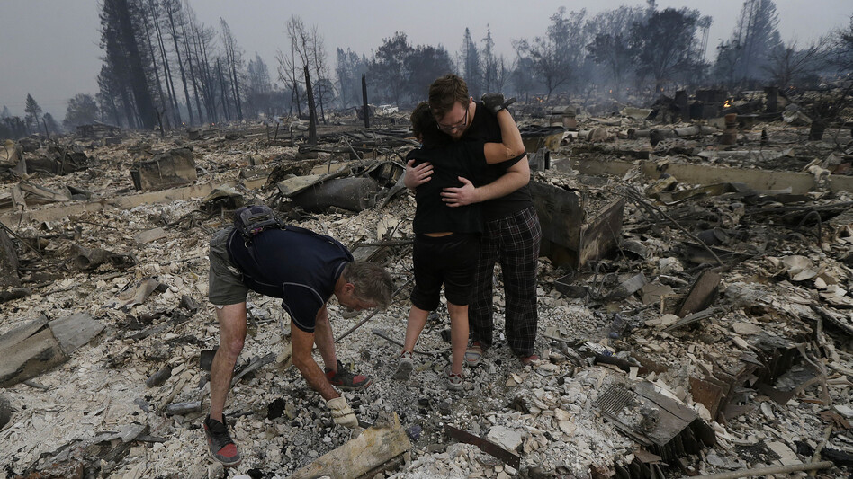 Michael Pond, left, looks through ashes as his wife Kristine, center, gets a hug from Zack Thurston, their daughter's boyfriend, while they search the remains of their home destroyed by fires in Santa Rosa, California. (Jeff Chiu/AP)