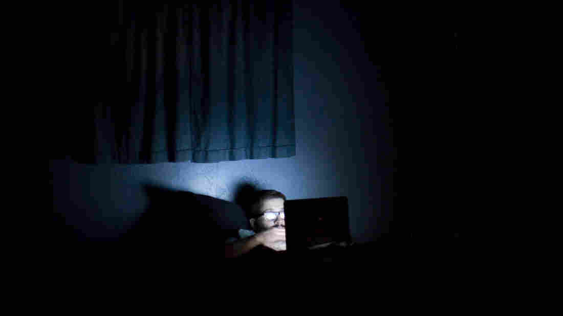A man surfs the Internet in a dark room