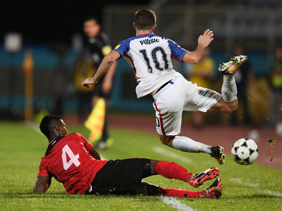 Team USA's Christian Pulisic is defended by Trinidad and Tobago's Kevon Villaroel on Tuesday night during their 2018 World Cup qualifier football match in Couva, Trinidad and Tobago. A loss, combined with other results, means the U.S. team will be staying home next year.