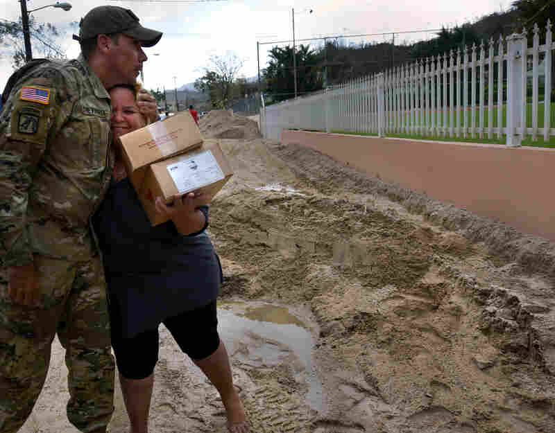 Sgt 1st Class Alejandro Echevarria hugs resident Glenda Montero as National Guard troops deliver aid needed on Avenida Esteves.