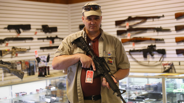 "Shop owner Jeff Binkley displays an AR-15 ""Sport"" rifle at Sarge"