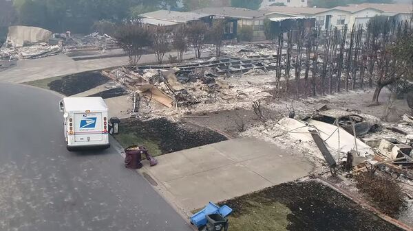Aerial drone footage shows a U.S. Postal Service mail carrier making the rounds in Santa Rosa, Calif., delivering mail at houses that were reduced to rubble by intense wildfires.