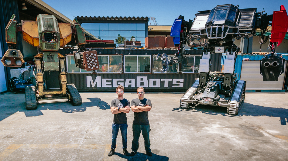 Matt Oehrlein and Gui Cavalcanti, co-founders of the robotics company, MegaBots, with giant robots MK2 (left) and Eagle Prime. (Greg Munson)
