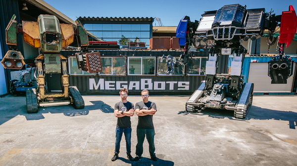 Matt Oehrlein and Gui Cavalcanti, co-founders of the robotics company, MegaBots, with giant robots MK2 (left) and Eagle Prime.