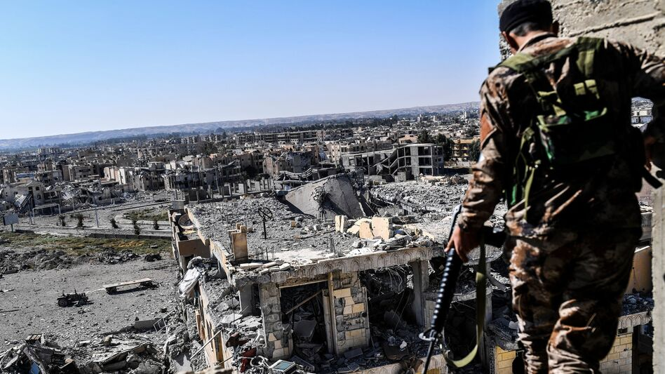 A member of the Syrian Democratic Forces walks on a building near Raqqa's stadium Monday, as they cleared the last positions on the front line in the fight against ISIS. (Bulent Kilic/AFP/Getty Images)