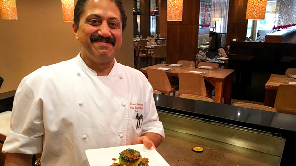 """Rasika chef Vikram Sunderam, here with a towering dish of eggplant and potato, says, """"Indian cuisine is a very personal cuisine. It"""