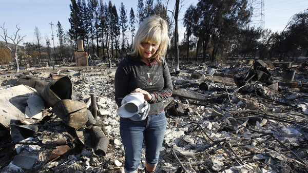 Debbie Wolfe looks at the antique pitcher that once belonged to her grandmother after finding it the burned ruins of her home on Tuesday in Santa Rosa, Calif.