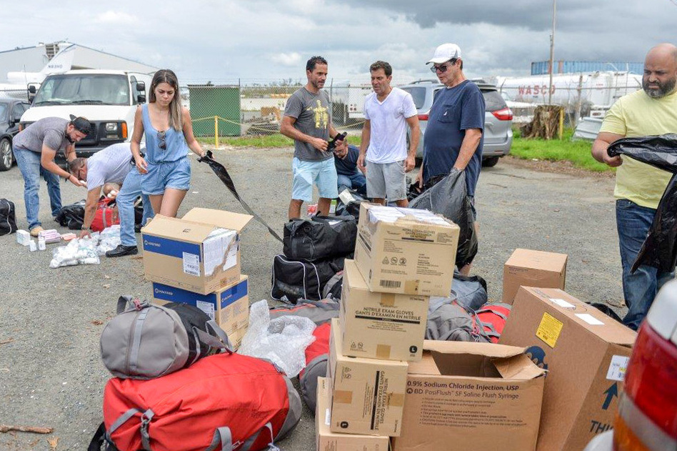 Together, José Ortíz (center left) and Ethan Leder (center right) — without the help of any major agency or aid organization — chartered a plane to Puerto Rico filled with donated medical supplies and get people with acute medical needs out of the island for treatment in the continental U.S. (Courtesy of Willin Rodriguez)