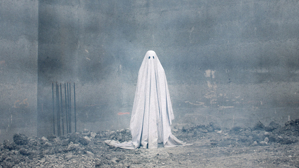 A ghost stands in the ruins of a demolished building in a scene from the film A Ghost Story.