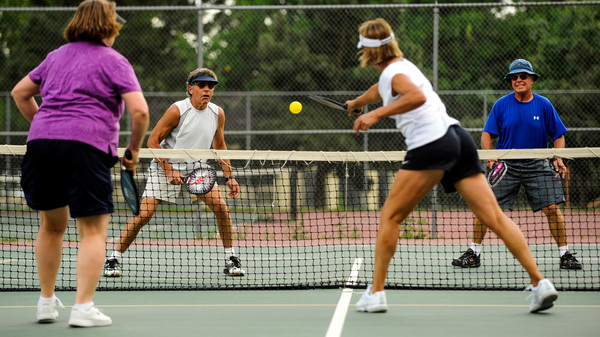 Val Olson (from left), Rick Kamm, Steve David and Dee Haskins play up to the net during a pickleball game at Monument Valley Park in Colorado Springs, Colo., in 2011.