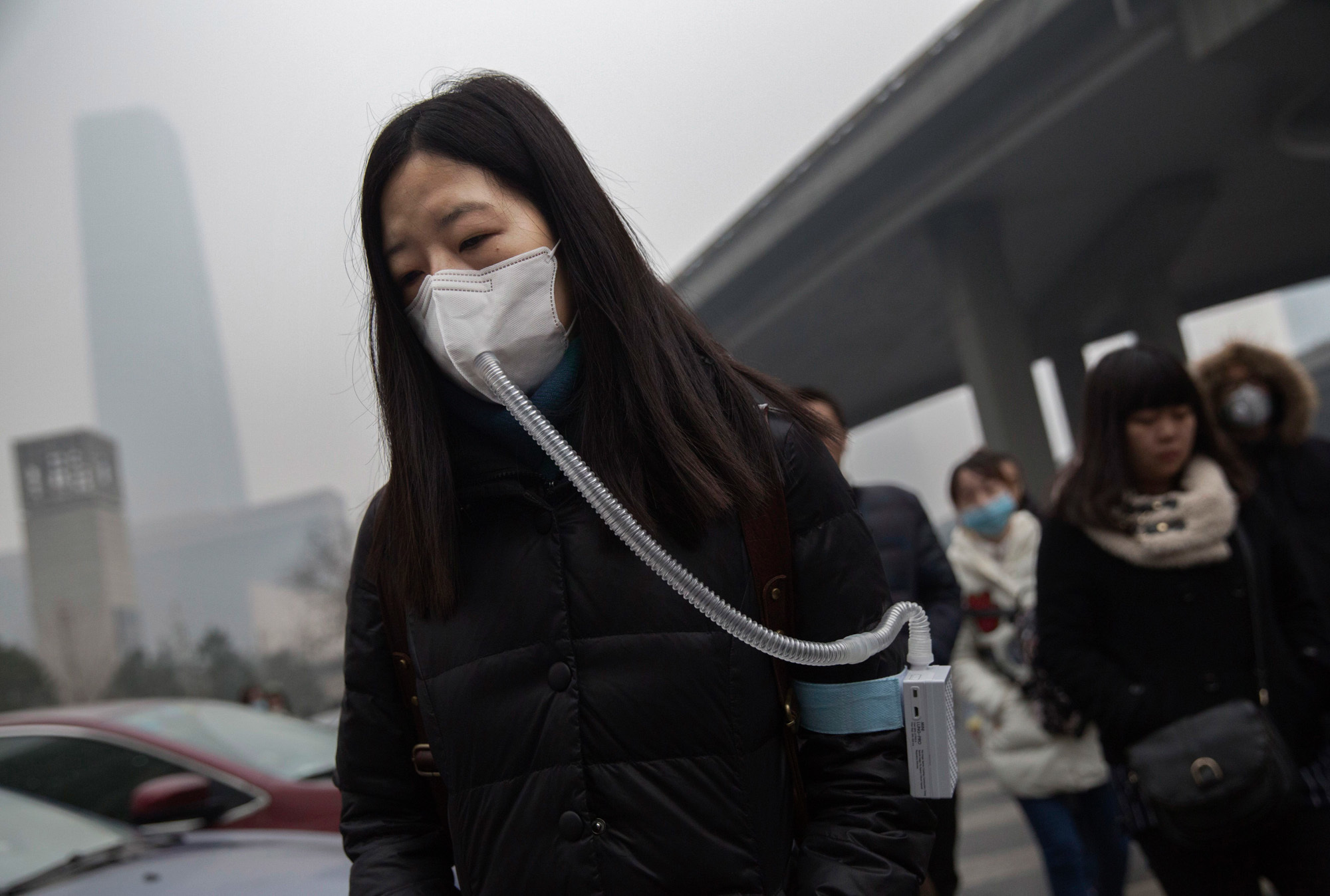 A woman wears a mask and filter as she walks to work during heavy pollution in Beijing China