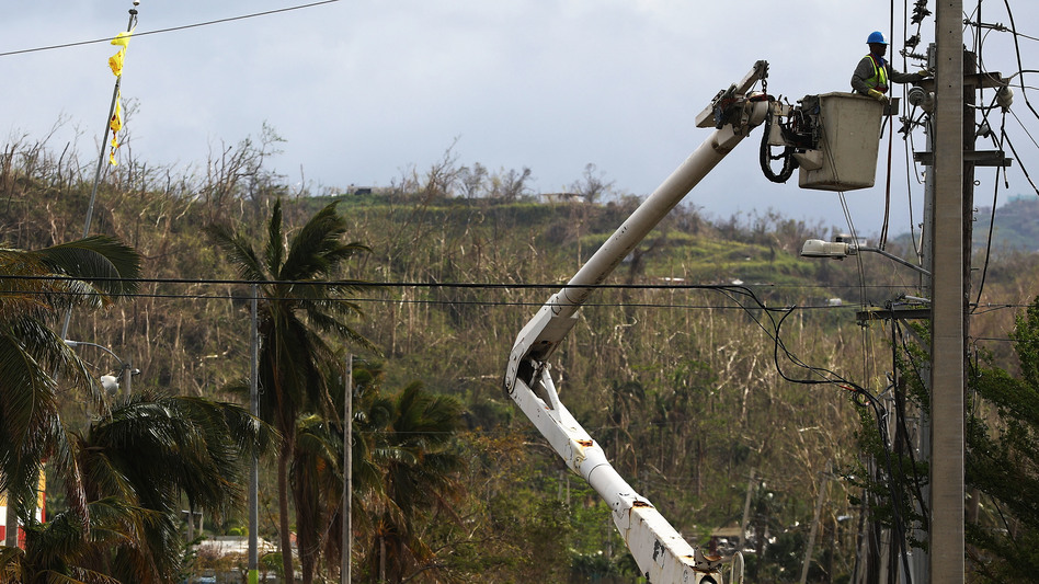 A worker repairs power lines in San Isidro, Puerto Rico. An outdated, aboveground power grid coupled with a comparative shortage of utility workers have hobbled efforts to restore power in the territory. (Mario Tama/Getty Images)