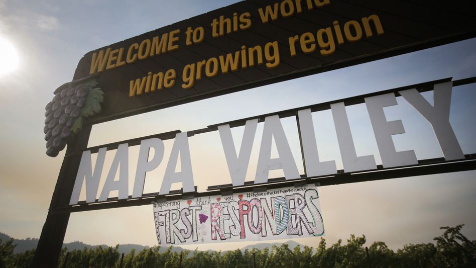 A handmade sign is seen attached to the Napa Valley welcome sign on Oct. 16, 2017 in Oakville, Calif. At least 40 people are confirmed dead, dozens are still missing, and at least 5,700 buildings have been destroyed since wildfires broke out a week ago. (Elijah Nouvelage/Getty Images)