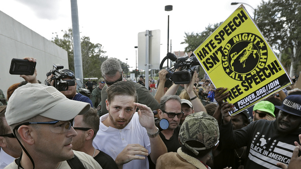 A supporter of white nationalist Richard Spencer (center in white shirt) tries to cover up as he clashes with the crowd after a speech by Spencer on Thursday at the University of Florida in Gainesville.