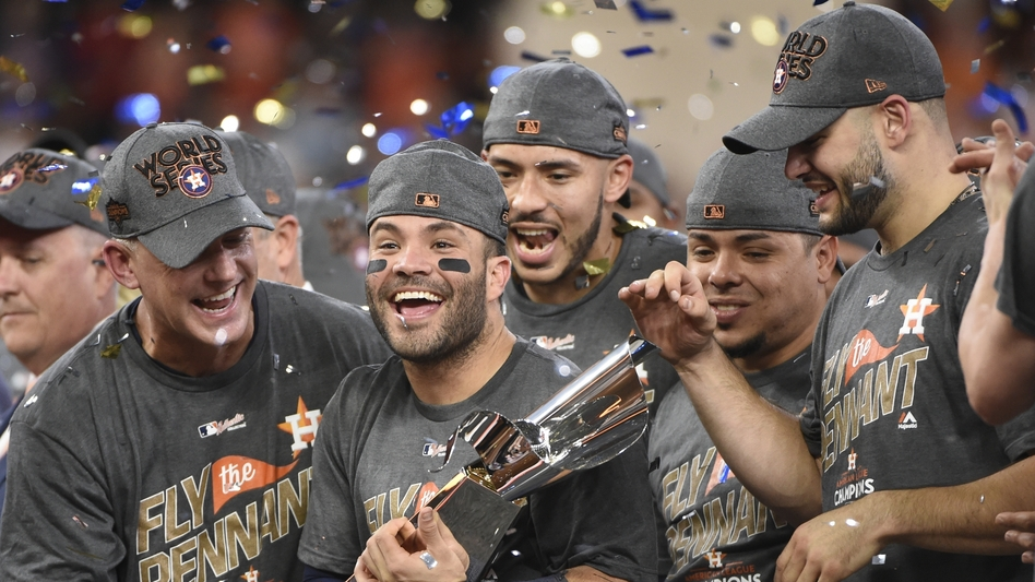 Houston Astros' Jose Altuve holds up the championship trophy after Game 7 of baseball's American League Championship Series against the New York Yankees Saturday in Houston. (Eric Christian Smith/AP)