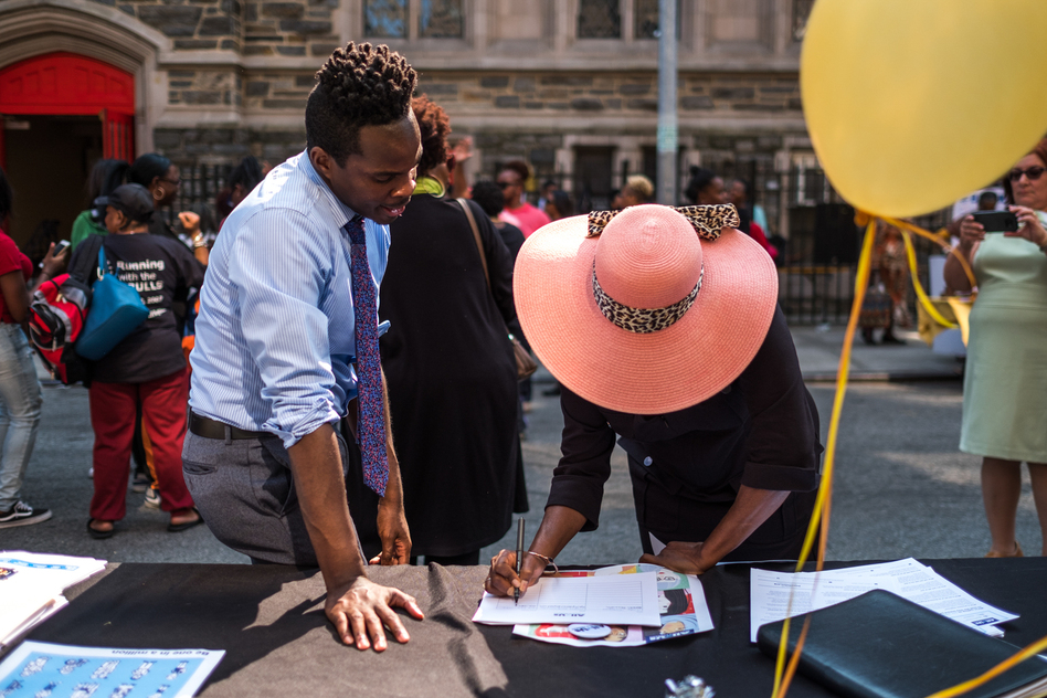 Kolbi Brown (left), a program manager at Harlem Hospital in New York, helps Karen Phillips sign up to receive more information about the All of Us medical research program, during a block party outside the Abyssinian Baptist Church in Harlem. (Elias Williams for NPR)
