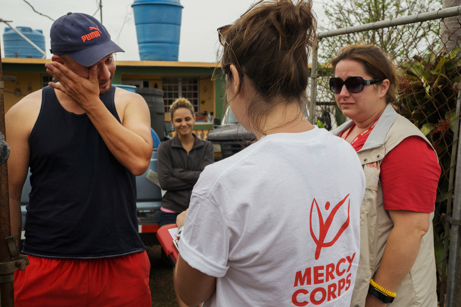 Argenis Ramos, 34, wipes a tear while answering questions for a field research survey by Mercy Corps staffers Alexa Swift (center) and Jill Morehead. Ramos' wife, Karian Batista, looks on. (Angel Valentin for NPR)