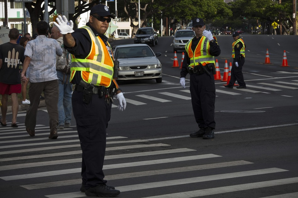 Honolulu police officers direct traffic at an intersection. Honolulu is the first major U.S. city to ban texting while walking in a crosswalk. (Kent Nishimura/AFP/Getty Images)