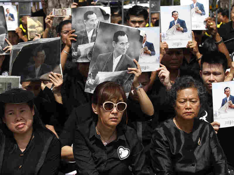 Mourners hold aloft the portraits of late Thai King Bhumibol Adulyadej during his funeral procession and royal cremation ceremony.