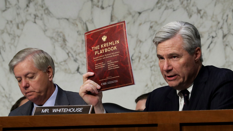 Senate Judiciary Committee member Sheldon Whitehouse, D-R.I., holds up a copy of The Kremlin Playbook while delivering remarks with Sen. Lindsey Graham, R-S.C., at the conclusion of a May 8 subcommittee hearing on Russian interference in the 2016 election. (Chip Somodevilla/Getty Images)