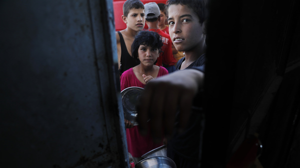 Syrian children who fled Raqqa, where the U.S.-backed Syrian Democratic Forces defeated the Islamic State group, are now living in a refugee camp. They hold pots as they line up for food.