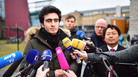 Anas Modamani speaks to the media Feb. 6 in Wuerzburg, Germany, after a court session about his lawsuit against Facebook. Modamani's suit, regarding the misuse of a selfie he took of himself with German Chancellor Angela Merkel was rejected, but his lawyer Lawyer Chan-Jo Jun, right, says that under a new law a lawsuit might not even have been necessary.