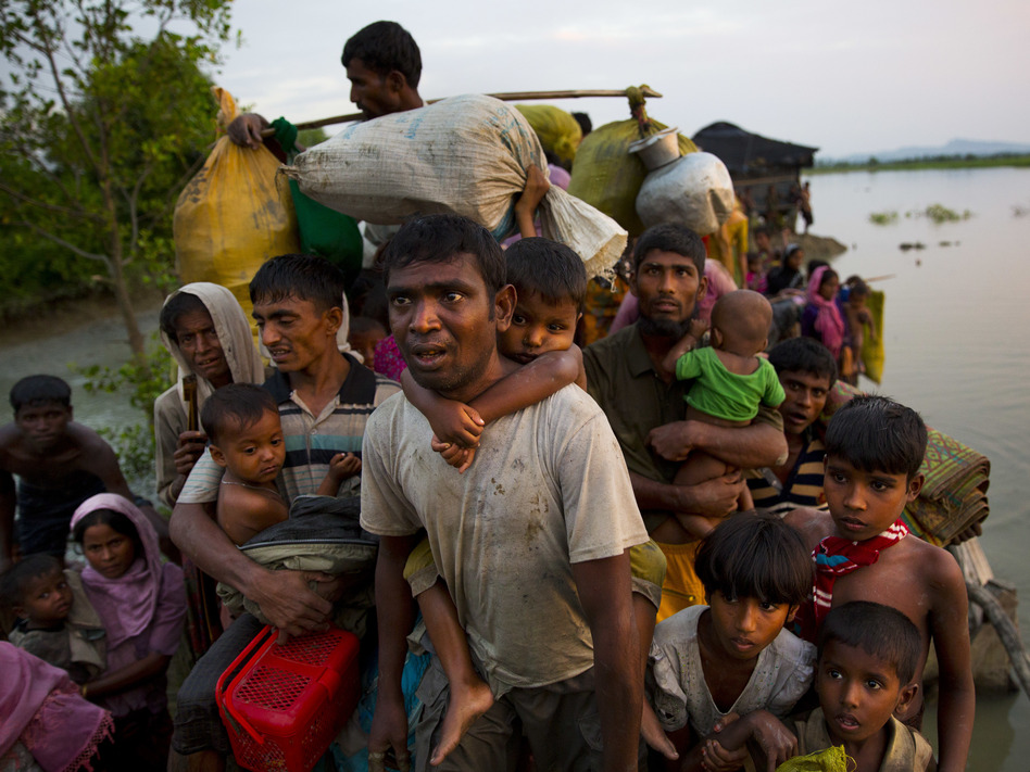 Rohingya Muslims carry their young children and belongings after crossing the border from Myanmar into Bangladesh, near Palong Khali, Bangladesh, on Wednesday. (Bernat Armangue/AP)