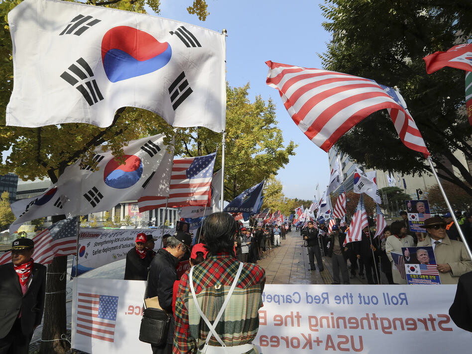 South Koreans hold flags during a rally welcoming U.S. President Donald Trump's visit to the country in downtown Seoul, South Korea, on Friday. (Lee Jin-man/AP)