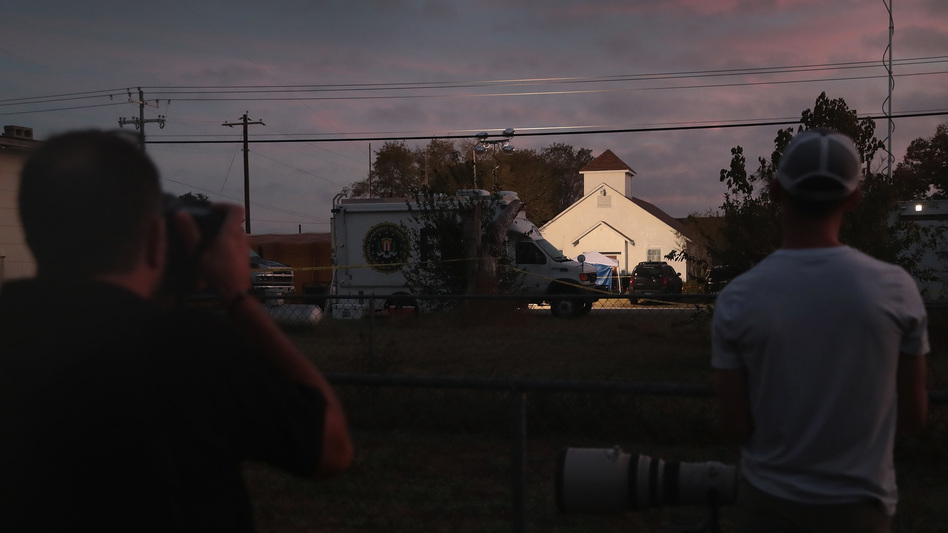 Newspaper photographers look on as the sun rises over the First Baptist Church in Sutherland Springs, Texas, the site of a mass shooting during a Sunday service. (Scott Olson/Getty Images)