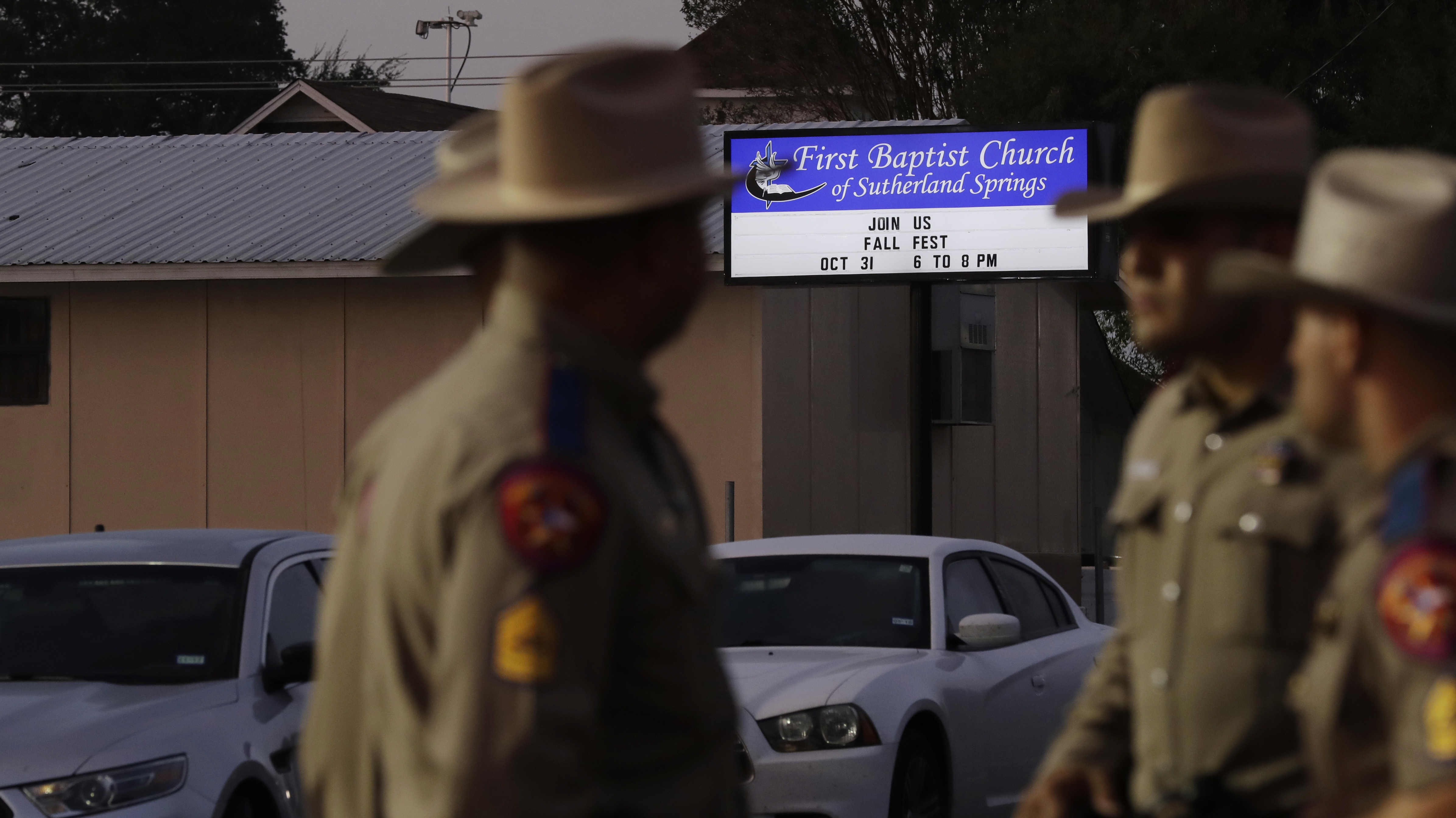 Law enforcement officials gather Monday at the scene of a deadly shooting the previous day at the First Baptist Church of Sutherland Springs in Texas.