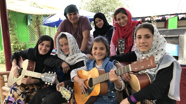 """The Miraculous Love Kids music school founder Lanny Cordola (top left) stands with Madina Mohammadi (top center), Mursal (top right) and other students outside their rehearsal space in Kabul. Their favorite song is """"Fragile"""" by Sting. """"What we"""