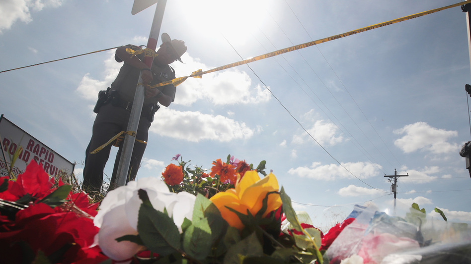 A police officer ties off crime scene tape near a small memorial close to the First Baptist Church of Sutherland Springs on Tuesday in Sutherland Springs, Texas. On Sunday, a gunman, Devin Patrick Kelley, killed 26 people at the church and wounded 20 more when he opened fire during a Sunday service. (Scott Olson/Getty Images)