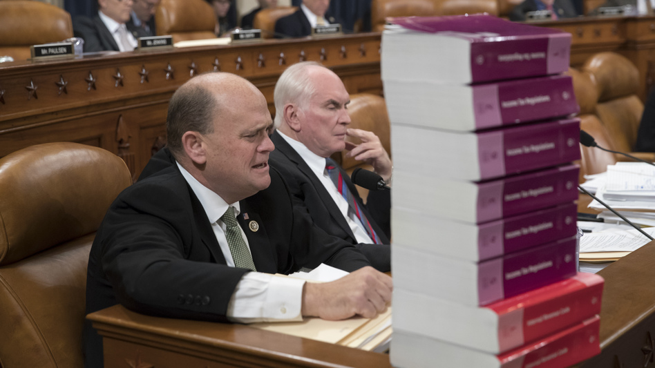 Seated behind a stack of IRS and tax volumes, Rep. Tom Reed, R-N.Y. (left), and Rep. Mike Kelly, R-Pa., attend a Ways and Means Committee debate on the GOP tax plan on Wednesday.