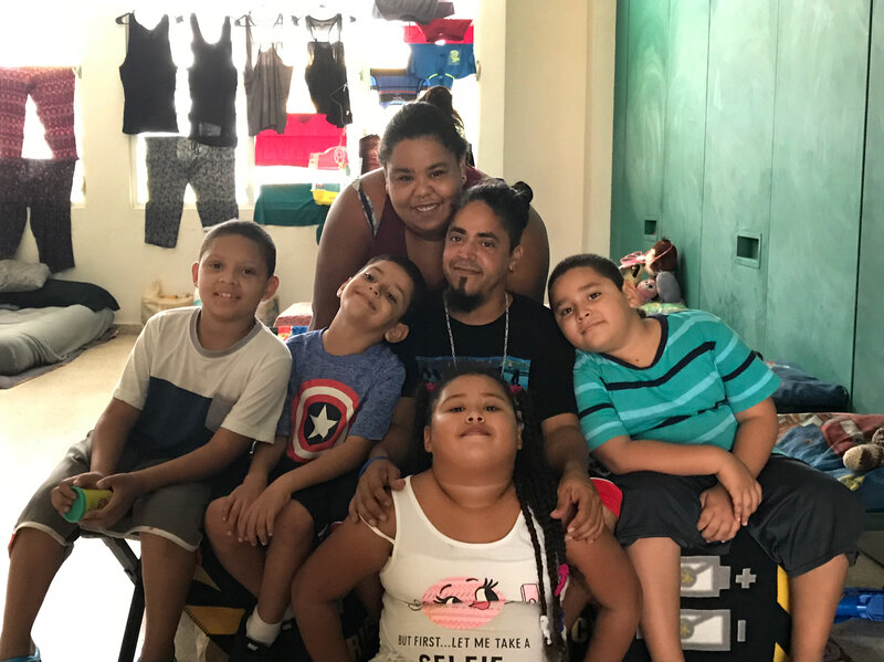 Chaylin Palma, her husband Miguel Nieves and their four children, (left to right) Johushua, Abimael, Chalyani and Miguel have been living in a shelter in a high school since their home was destroyed in Hurricane Maria.     Greg Allen/NPR