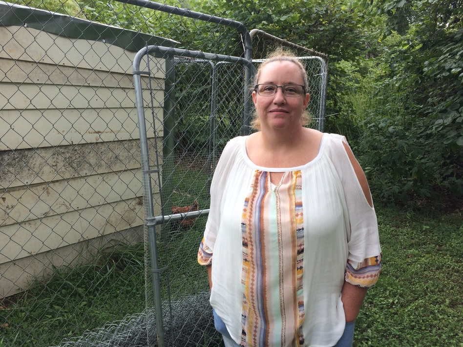 Medical debts weigh on Geneva Wilson, who keeps a chicken and rooster in a coop behind her cabin in rural southwest Missouri.