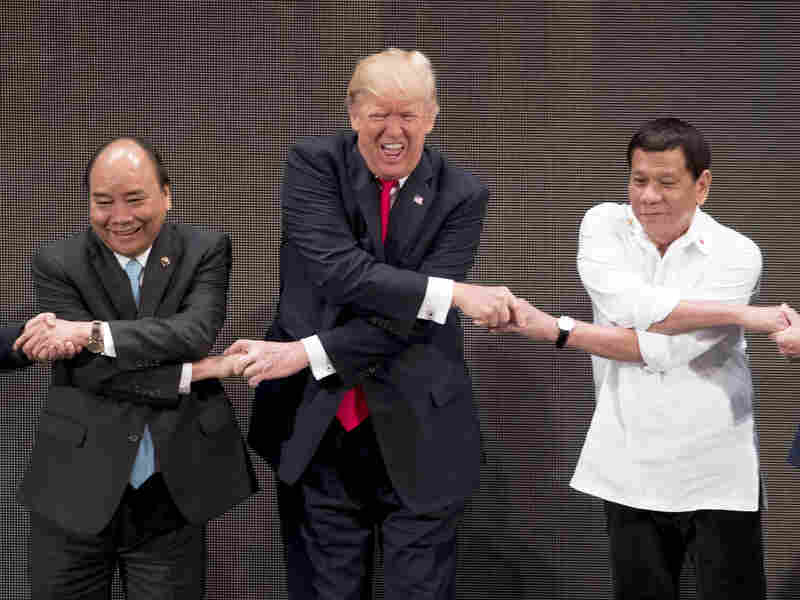 "President Trump reacts as he does the ""ASEAN-way handshake"" with Vietnamese Prime Minister Nguyen Xuan Phuc (left) and Philippine President Rodrigo Duterte on stage during the opening ceremony at the ASEAN Summit at the Cultural Center of the Philippines on Monday."